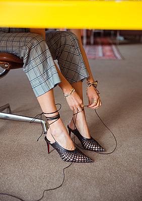 Junge Frau bindet sich die High Heels zu - p432m2027613 von mia takahara