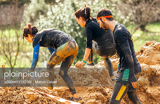 Participants in extreme obstacle race, running through mud