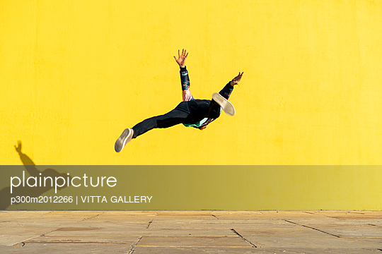 Acrobat jumping somersaults in front of yellow wall - p300m2012266 von VITTA GALLERY