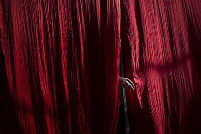 Outstretched hand between red curtain - p1007m2099028 by Tilby Vattard