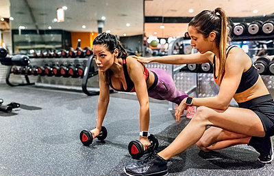 Woman with her trainer working out in gym - p300m1449273 by Marco Govel