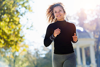 Smiling young woman with earphones running in park - p300m1562899 by Josep Suria