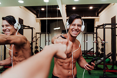 Cheerful sportsman with headphones and mobile phone giving fist bumps to friend in gym - p300m2274575 by Eva Blanco