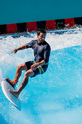 Madrid, Spain. Young man surfing in indoor sports facilities. - p300m2276955 von Manu Reyes