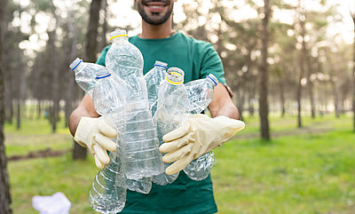 Male volunteer holding plastic bottles while cleaning forest - p300m2282009 by Jose Carlos Ichiro