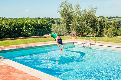Woman diving into swimming pool - p352m2120220 by Anna Larsson