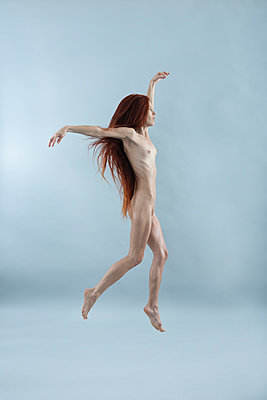 Naked woman with red hair dances with arms outstretched - p427m2244990 by Ralf Mohr