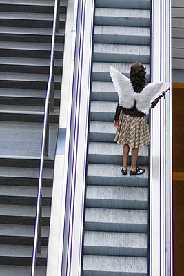 Woman with angel wings on escalator - p4903098 by Felbert+Eickenberg