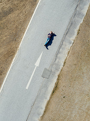 Man on country road lies next to directional arrow, aerial view - p586m1088343 by Kniel Synnatzschke
