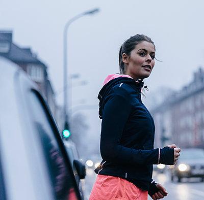 Young woman crosses main road - p586m1539577 by Kniel Synnatzschke