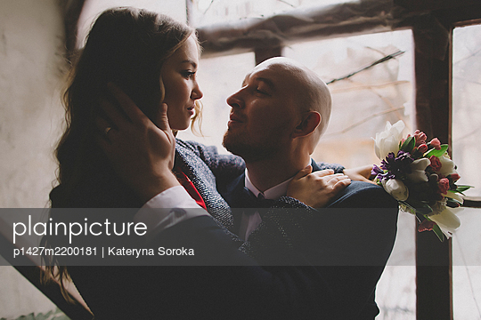 Newlywed couple embracing in window - p1427m2200181 by Kateryna Soroka