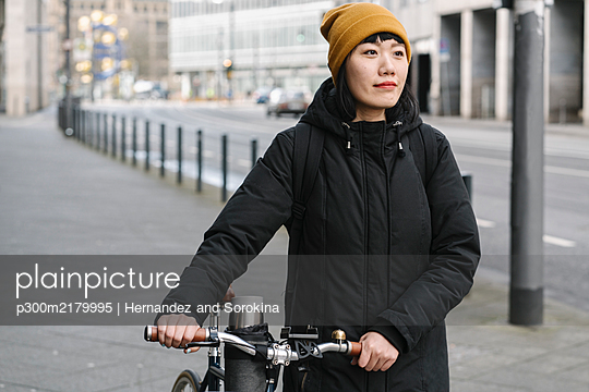 Woman with bicycle in the city, Frankfurt, Germany - p300m2179995 by Hernandez and Sorokina