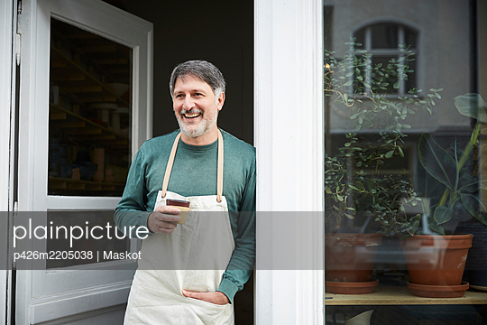 Smiling mature male owner looking away while having coffee at doorway of art studio - p426m2205038 by Maskot