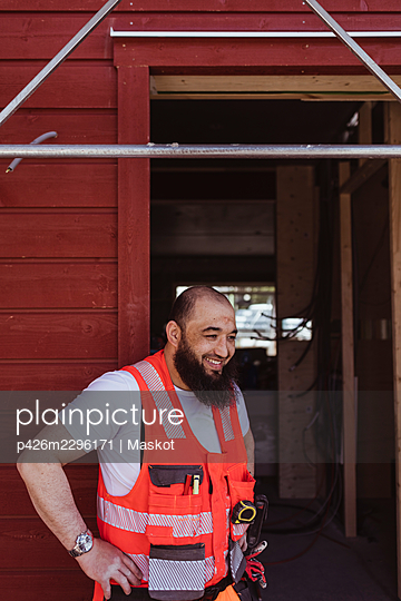 Smiling bearded male construction worker standing with hand on hip at doorway - p426m2296171 by Maskot