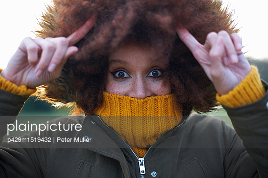 Portrait of young woman outdoors, wrapped up warm - p429m1519432 by Peter Muller