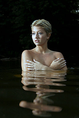Woman standing in the water - p1019m739841 by Stephen Carroll