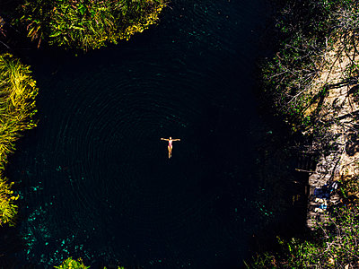 From above female with outstretched arms enjoying bath in clean Cenote - p1166m2137541 by Cavan Images
