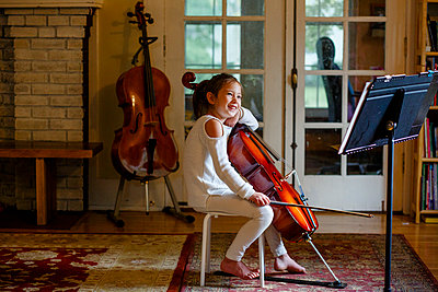 A happy barefoot girl practices her cello in the living room - p1166m2279445 by Cavan Images