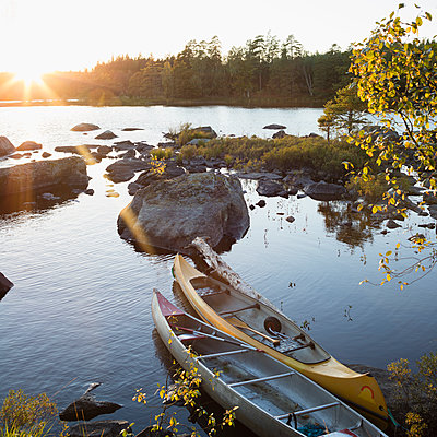 Sweden, Skane, Filkesjon, Canoes moored at shore - p352m1126834f by Gustaf Emanuelsson