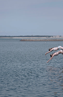 Two girls jumping into water - p444m960706 by Müggenburg