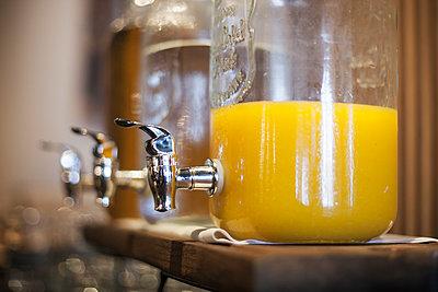 Orange juice in glass dispenser - p623m1495180 by Gabriel Sanchez
