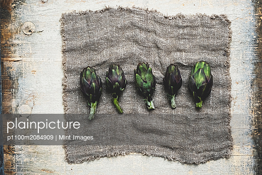 High angle close up of fresh artichokes on grey cloth. - p1100m2084909 by Mint Images
