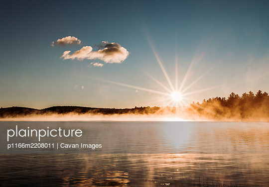 rising sun star over peaceful misty and foggy lake in Maine woods - p1166m2208011 by Cavan Images