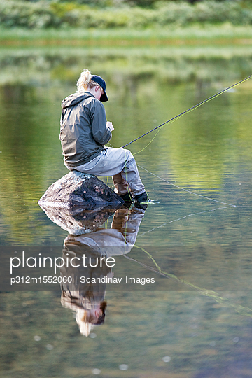 plainpicture - plainpicture p312m1552060 - Woman fishing in river or lake - plainpicture/Johner/Scandinav Images