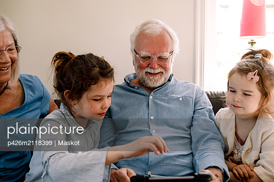 Smiling grandparents sitting with grandchildren while looking at digital tablet in living room at home - p426m2118399 by Maskot