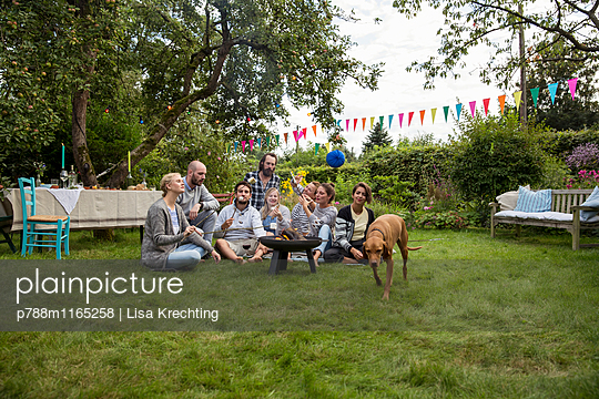 Friends roasting marshmallows in the allotment garden - p788m1165258 by Lisa Krechting
