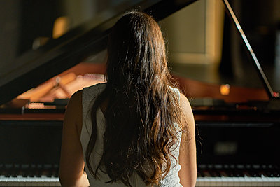 A woman with her back dressed in a white dress playing a black grand piano with the lid lifted - p1166m2152144 by Cavan Images