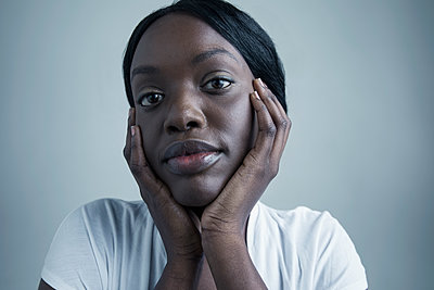Close up portrait serious African American young woman with head in hands - p1192m1213187 by Hero Images