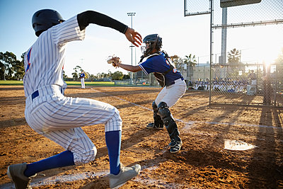 Baseball player sliding into home plate - p1192m2062505 by Hero Images