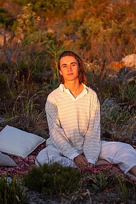 Teenage boy sits on blanket in a meadow - p1640m2245950 by Holly & John