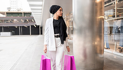 Thoughtful Arab woman wearing headscarf holding bags while shopping at mall - p300m2266376 by Jose Carlos Ichiro