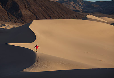 A man running on sand dunes in the desert. - p343m1184569 by Woods Wheatcroft