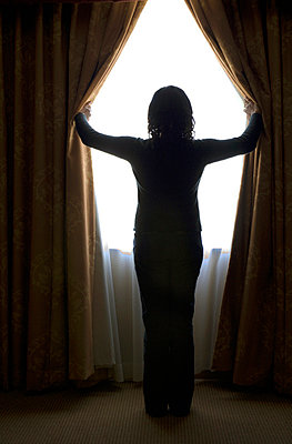 Woman opening curtains, looking out window - p3720372 by James Godman
