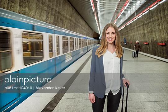 Frau lächelt an einem Bahnhof - p081m1124910 von Alexander Keller