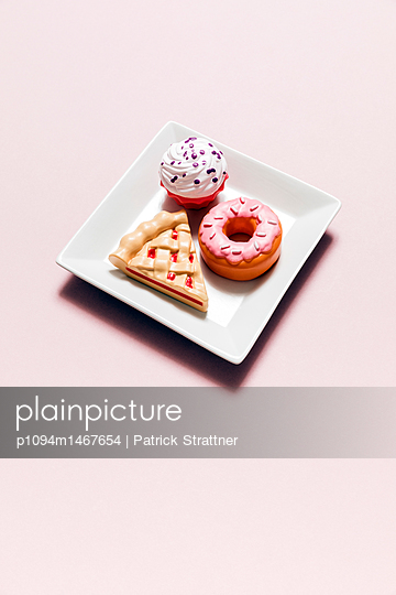 High angle view of desert toys in plate on pink background - p1094m1467654 by Patrick Strattner