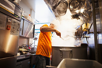 The ramen noodle shop kitchen. A vast pot on the stove, and steam rising.  A man cooking noodles..  - p1100m1185661 by Mint Images