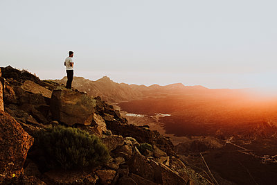 A man stands on mountain top watching sunset - p1166m2129935 by Cavan Images