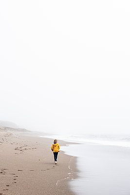 Teenager walks along oceans edge on quiet beach - p1166m2153454 by Cavan Images