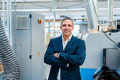 Portrait of a confident businessman in a factory - p300m2159988 by Daniel Ingold