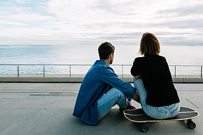Couple sitting on ground in skateboard, facing sea - p300m2257441 by Xavier Lorenzo