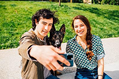 Couple outdoor having fun with dog - Italy, Lombardy, Milan - companion, friendship, family concept - p300m2290669 von Eugenio Marongiu