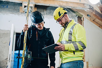 Male construction workers discussing over digital tablet while working at site - p426m2296086 by Maskot
