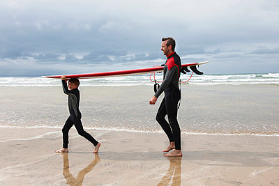 Father and Son carrying surf board - p42911812f by Adie Bush