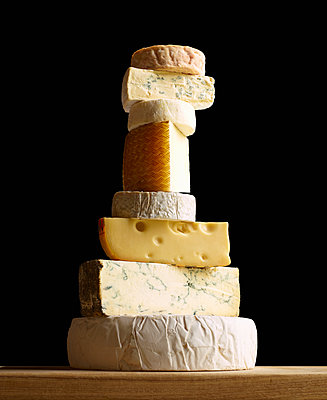 Stack of selection of cheeses, against black background - p429m1408087 by Tim MacPherson
