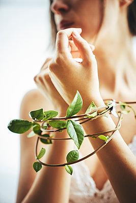 Kletterpflanze umschlingt Hände einer Frau - p968m2020233 von roberto pastrovicchio