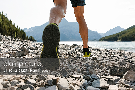 Man running over rocks along sunny lakeside - p1192m2129227 by Hero Images